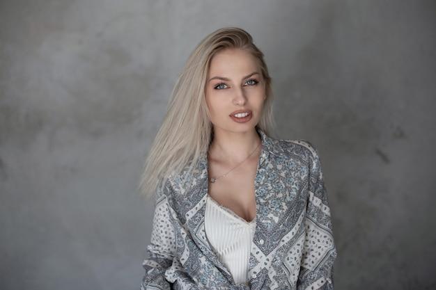 屋内のヴィンテージの灰色の壁の近くにスタイリッシュなtシャツを着たファッショナブルなシャツにセクシーな唇と青い目をしたブロンドの髪の自然なメイクのかなり若い女性