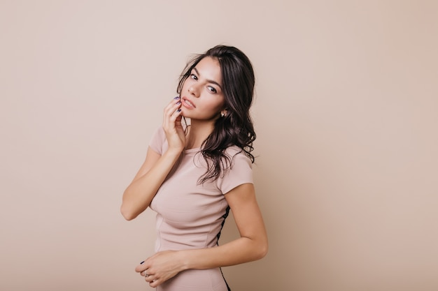 누드 메이크업을 가진 예쁜 젊은 여자가 다루어 보인다. 갈색 눈을 가진 어두운 머리 곱슬 아가씨의 초상화.