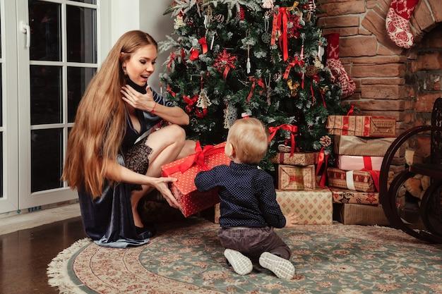 Довольно молодая женщина с годовалым ребенком играет у елки в гостиной. мама с милым сыном в комнате, украшенной рождеством. они улыбаются и счастливы. концепция семейного нового года. копировать пространство
