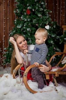 クリスマス ツリーで遊ぶ 1 歳の子供を持つかわいい若い女性。クリスマスの装飾が施された部屋でかわいい息子を持つママ