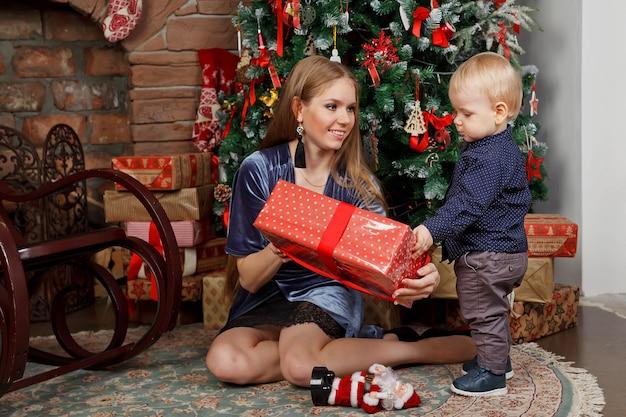 新年のツリーで遊ぶ 1 歳の子供を持つかわいい若い女性