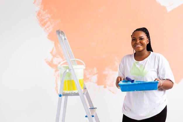 Довольно молодая женщина с малярным валиком в помещении