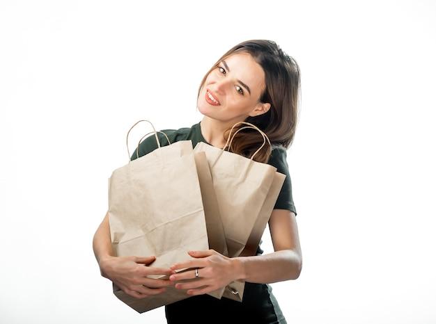 종이 쇼핑백과 함께 꽤 젊은 여자. 흰 바탕. 갈색 종이 가방을 껴안고 행복 웃는 아가씨.