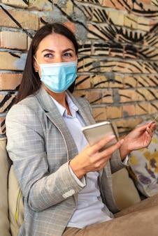カフェで携帯電話とクレジットカードを使用して保護フェイスマスクを持つかなり若い女性