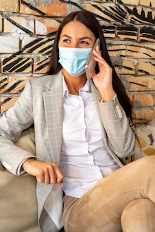 カフェで携帯電話を使用して保護マスクを持つかなり若い女性
