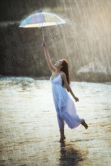 Pretty young woman with rainbow umbrella, under summer rain