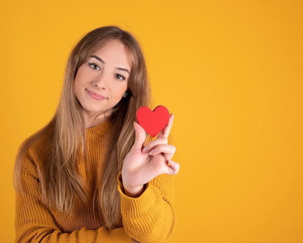 Pretty young woman with a red heart in her hands, yellow space