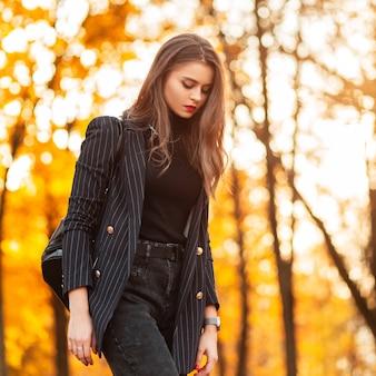 블레이저, 검은색 스웨터, 가죽 배낭을 메고 패션 우아한 정장을 입고 붉은 입술을 가진 예쁜 젊은 여성이 해질녘 노란색 단풍이 있는 놀라운 공원을 산책합니다. 여성의 비즈니스 스타일