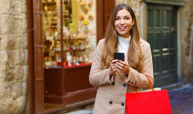 Довольно молодая женщина с хозяйственными сумками делает покупки онлайн с умным телефоном на улице во время рождества, глядя в камеру.