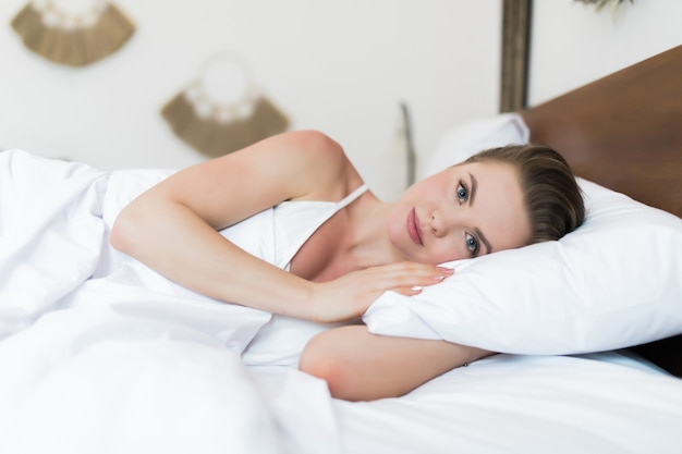 Pretty young woman with smile lying on the bed