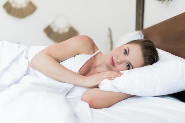 Довольно молодая женщина с улыбкой, лежа на кровати