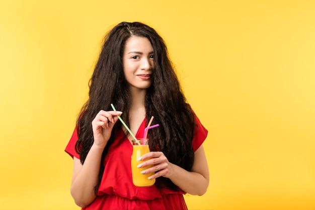 フレッシュジュースのストローボトルを持つかなり若い女性。健康的な栄養ライフスタイルオーガニックデトックスフルーツスムージークレンジングドリンク