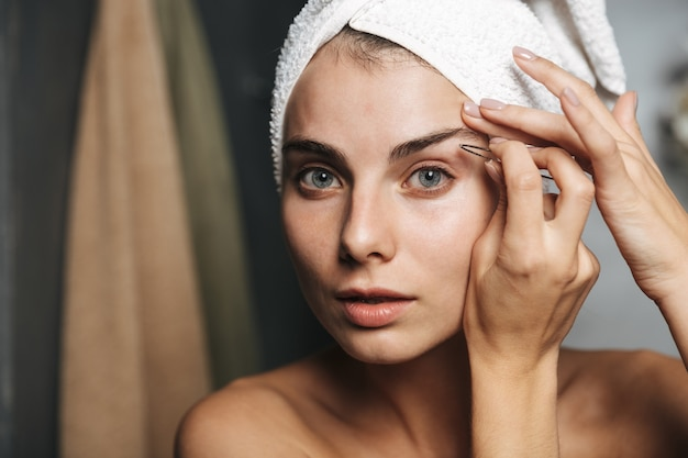 Pretty young woman with towel on head correcting eyebrows with tweezers in front of mirror in bathroom