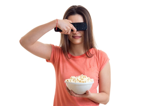 Pretty young woman with tv remote control and pop-corn in hands isolated on white