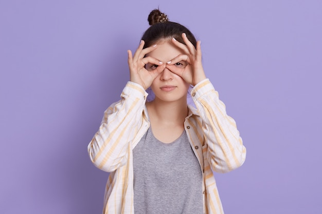 Pretty young woman with upset face holding fingers near eyes like glasses