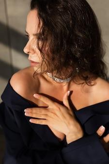 Довольно молодая женщина с мокрыми волосами позирует в студии, одетая в черный свободный пиджак и блестящее ожерелье