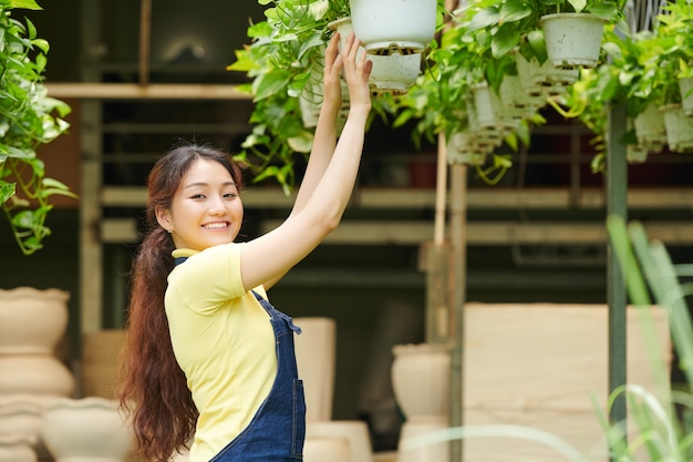 Pretty young woman working at gardening center, she is hanging pots with flowers and smiling at camera