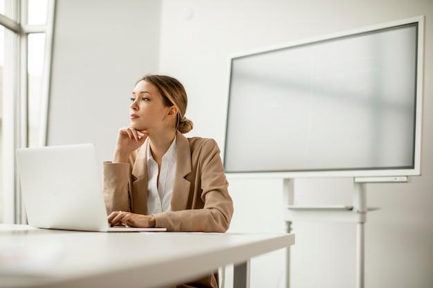 Довольно молодая женщина, работающая на ноутбуке в ярком офисе с большим экраном позади нее
