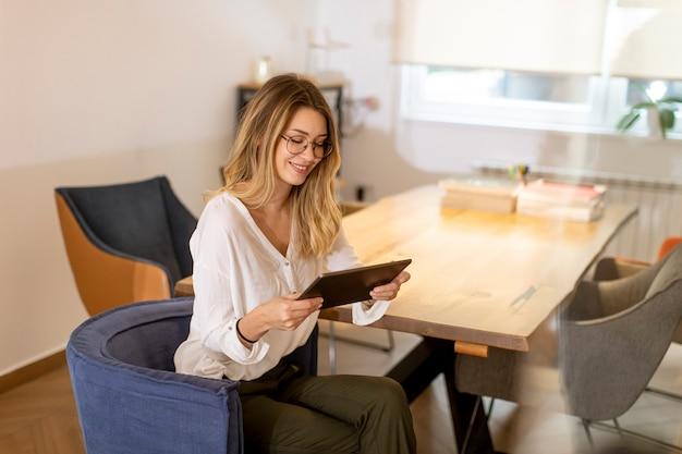 Довольно молодая женщина, работающая с цифровым планшетом в офисе