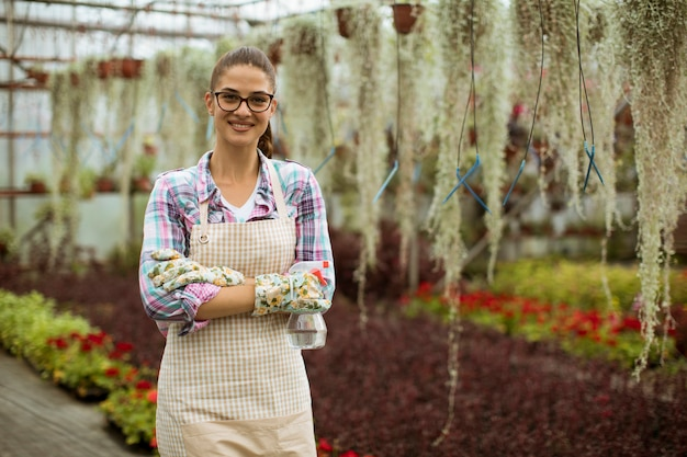 Pretty young woman working with spring flowers in the greenhouse