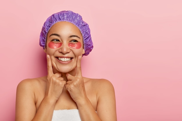 Pretty young woman wrapped in soft towel, cares about skin, wears hydrogel recovery patches or collagen pads, touches cheeks with index fingers, wears bath cap, shows bare shoulders, healthy skin