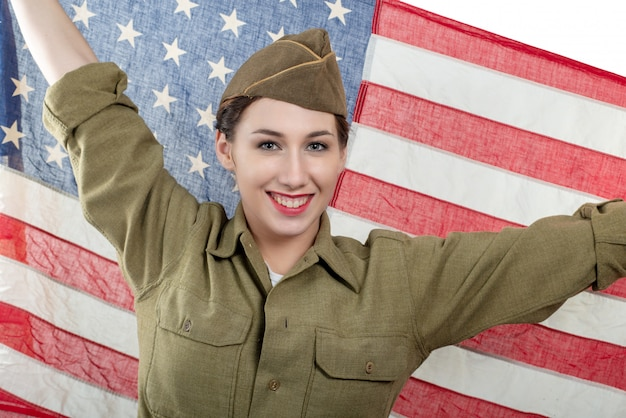 Pretty young woman in ww uniform us with american flag