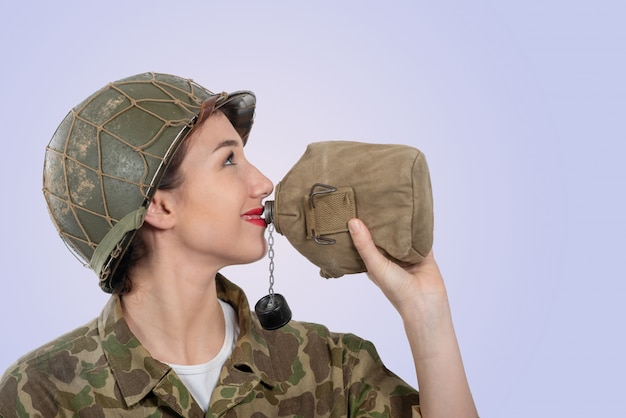 Pretty young woman in ww2 american uniform drinking water