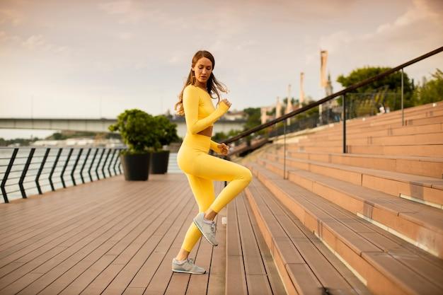 Довольно молодые женщины делают упражнения на лестнице у набережной реки