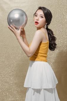 かなり若い女性が誕生日を祝い、銀のパーティー風船を持っています。