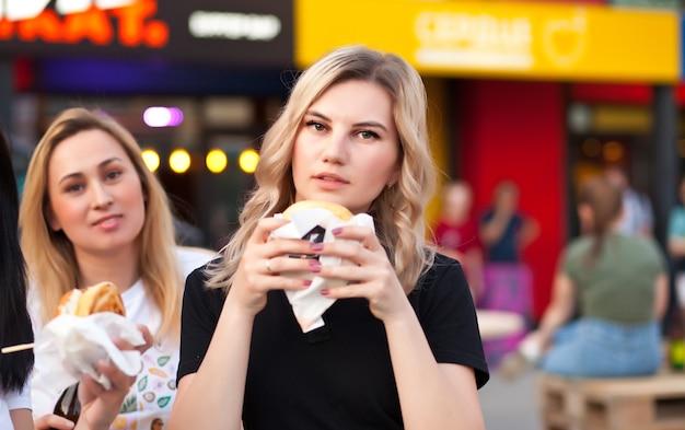 거리에서 야외에서 햄버거를 먹는 예쁜 젊은 여성.
