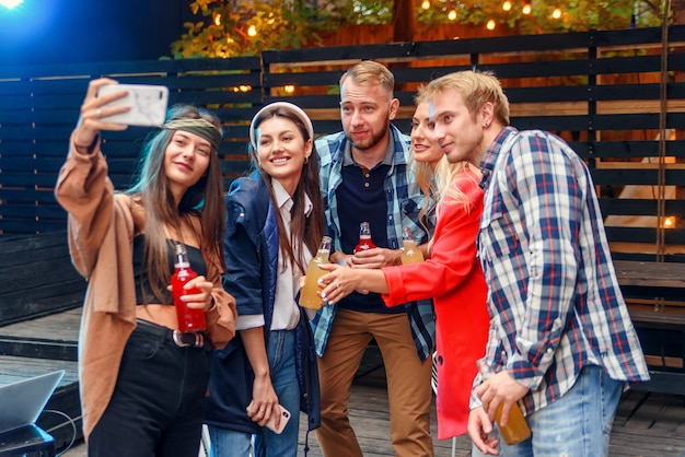 Pretty young women and handsome guys at celebration party making selfie photo on smartphone.
