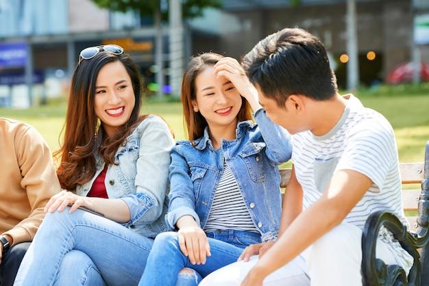 晴れた日に屋外で休んでいるときに友達の冗談を笑っているかなり若い女性