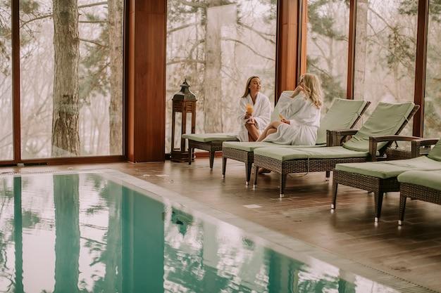 Довольно молодые женщины отдыхают на шезлонге у бассейна