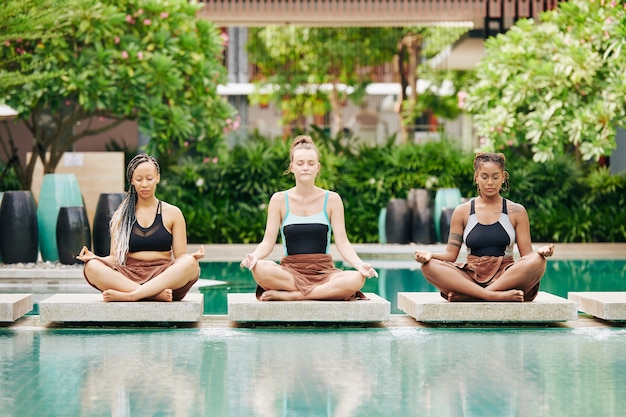 Pretty young women in swimsuits sitting in lotus position and doing breathing exercise to calm down and meditate