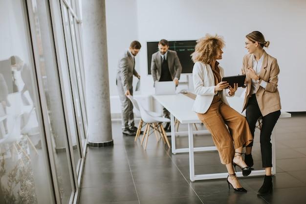 Довольно молодые женщины, использующие цифровой планшет в современном офисе перед своей командой