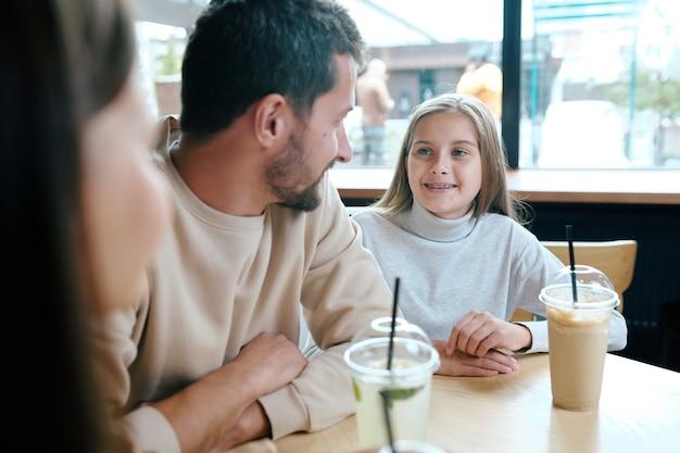 Довольно молодая девушка разговаривает со своим отцом, сидя за столиком в кафе и выпивая на досуге молочные коктейли