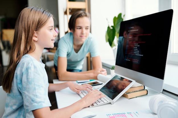 Довольно молодая девушка печатает на клавиатуре рабочего стола компьютера, глядя на монитор и готовит домашнее задание