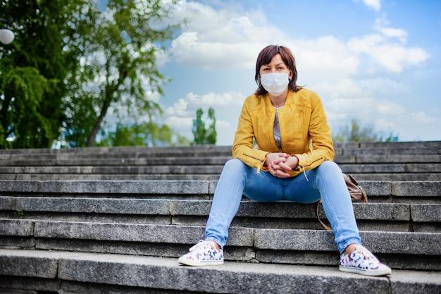 カジュアルな服を着た白い医療マスクのかなり若い中年女性が階段に座っています