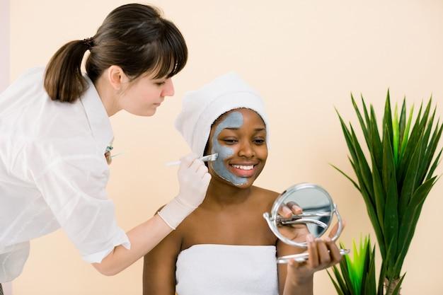 顔のルーチン、マスクを適用、鏡で見ている間に白いタオルでかなりypungアフリカの女性。スパサロンでアフリカ系アメリカ人女性の顔にマスクを適用する美容師
