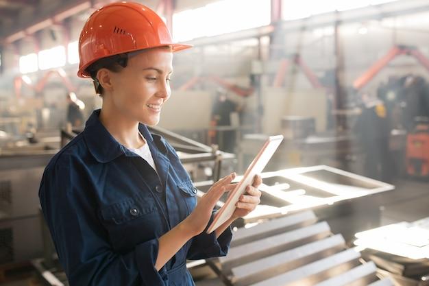 Симпатичная женщина-инженер или техник в униформе и шлеме сёрфит в сети в поисках онлайн-данных