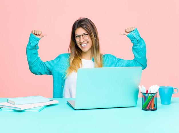 自信を持って、pretty慢と自信を持って、満足と成功を探して、自己を指しているラップトップで働く若いきれいな女性