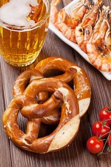 木製のテーブルにプレッツェル、ビールジョッキ、エビのグリル