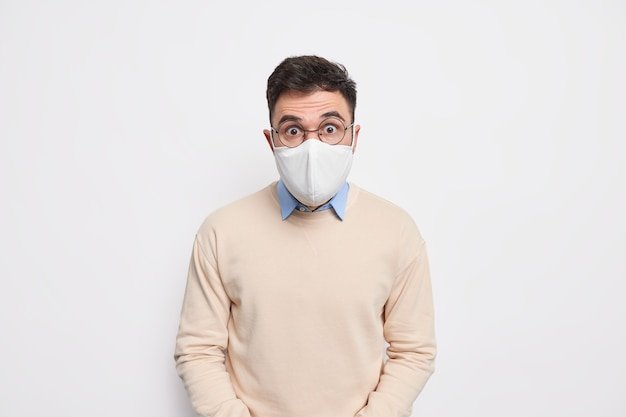 Предотвратить распространение вируса. шокированный мужчина в маске рекомендует носить защитные меры во время пандемии коронавируса, одетый в свитер Premium Фотографии