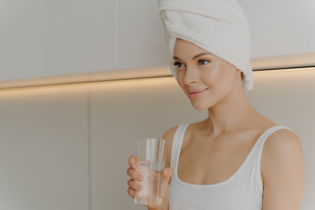 탈수 예방. 밝은 색의 부엌에 앉아 머리에 수건을 감고 샤워 직후 아침에 신선하고 빛나는 피부 식수를 가진 젊은 아름다운 여성의 이미지