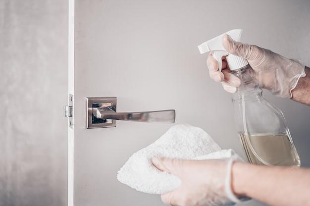 Профилактическая уборщица вытирает дверную ручку антибактериальным дезинфицирующим спреем для уничтожения коронирусного вируса на соприкасающихся поверхностях или прикосновения к ручке общественной ванной комнаты тканью.