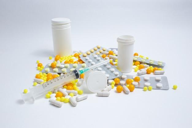 Профилактика, лечение гриппа, коронавируса. разноцветные таблетки, капсулы на белом