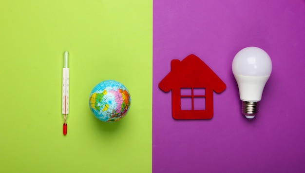 Prevention of global warming. eco, energy save concept. figurine of house with led light bulb, globe with a thermometer on green purple background.