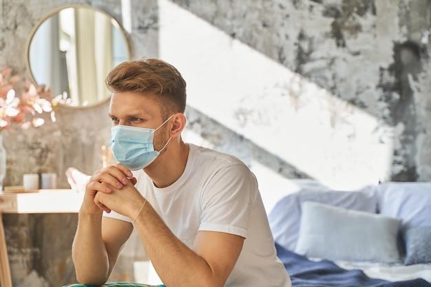 予防策。検疫中に保護医療マスクを着用している集中した若い男。ホームコンセプト