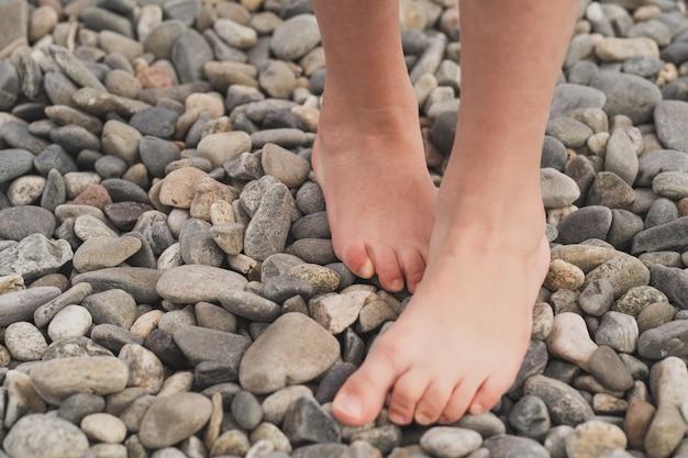 子供の扁平足の予防子供は裸足で石の上を歩きます。