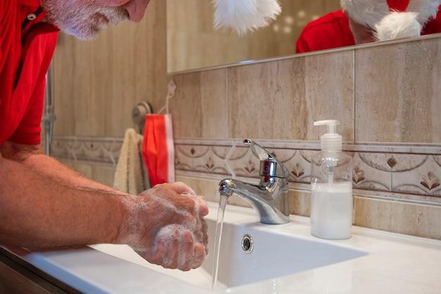 Предупреждение пандемии коронавируса. пожилой мужчина моет руки дома с рождественской шапкой на голове. сосредоточьтесь на пенке. красная хирургическая маска, висящая на стене